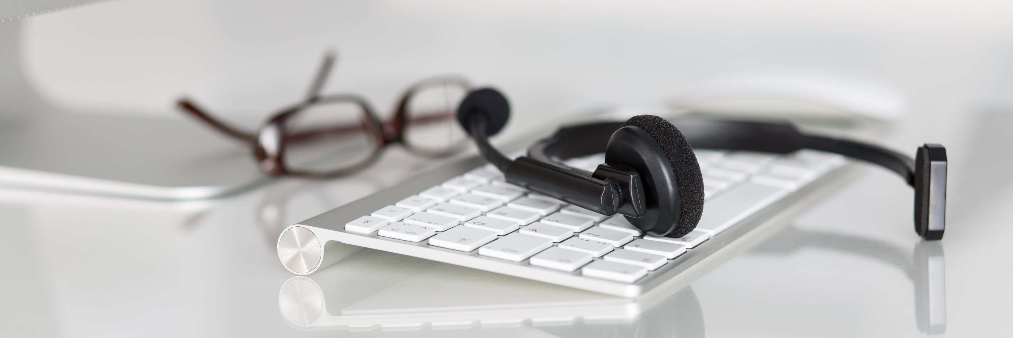 Call center service operator empty working place. Headset, glasses, keyboard at helpdesk employee workplace. Effective and efficient business information, help and support concept. Letterbox view